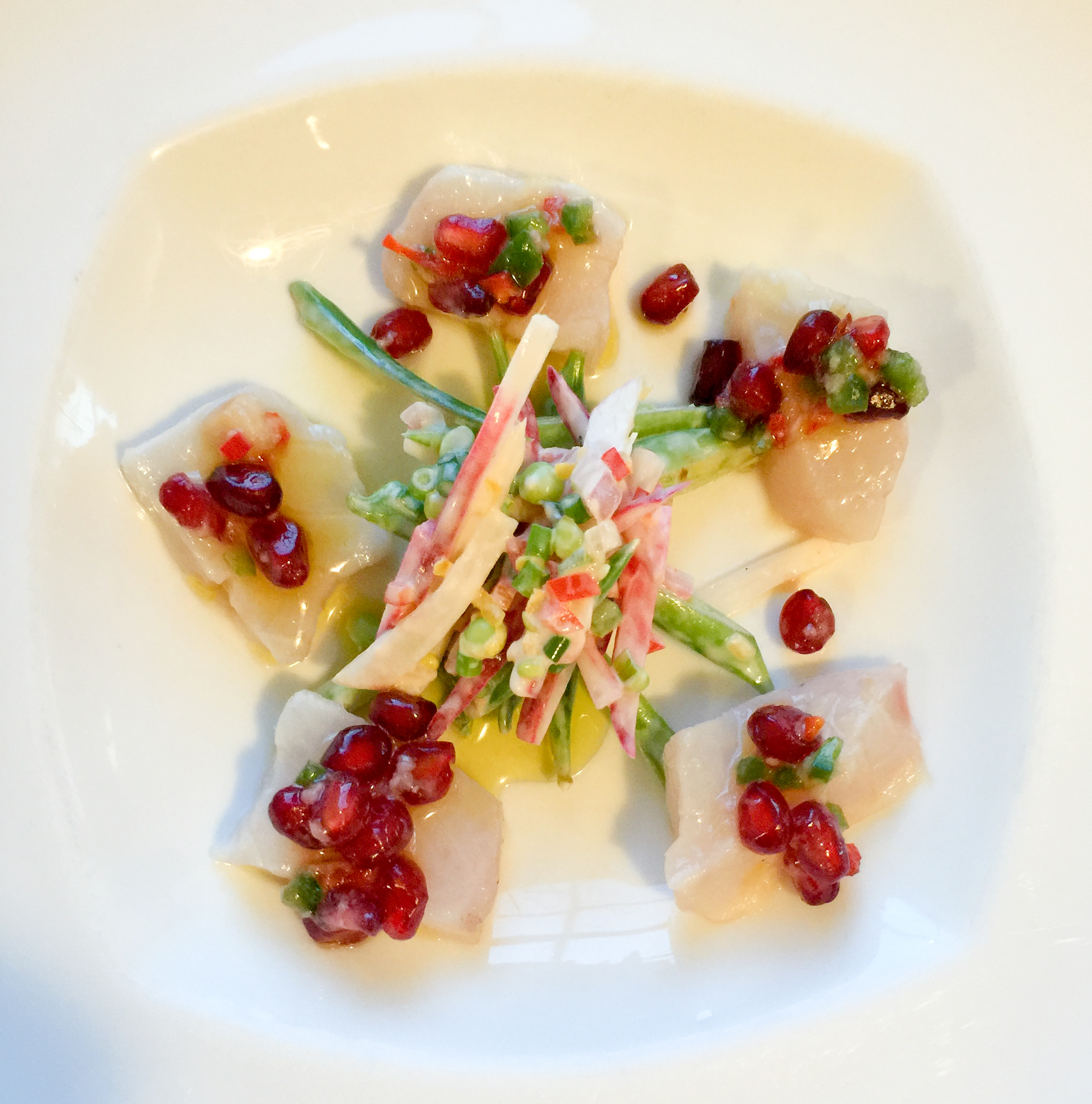 Striped bass crudo with pomegrante seeds and snap pea slaw